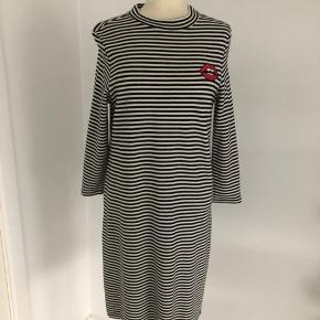 Smart kjole med sorte og råhvide striber fra EDC by Esprit med rød mund ved venstre kraveben.  Lange ærmer og lukning med skjult lynlås i ryggen.  Længde fra skulder er 95 cm, brystmålet er 96 cm, og taljen måler 90 cm.  Fremstillet af bomuld, og der er stretch i.  Bærer ikke præg af brug.