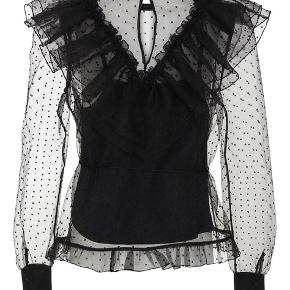 Overdådig mesh tyl bluse med prikker. Detaljeret med flæser og et bånd, som kan bindes i taljen. 100% polyester / Slip top: 95% viskose, 5% elastan Bytter desværre ikke..