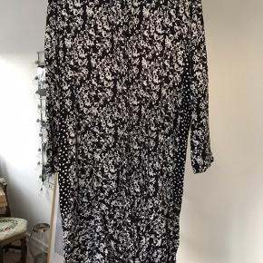 Sort skjortekjole med hvide blomster.  Prikket print under ærmer og langs siden.  Størrelsessvarende.  Længde: under knæ