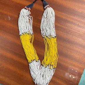 Varetype: flot statement halskæde, Day Nagas Farve: gul hvid sort Oprindelig købspris: 999 kr.  Flot, flot halskæde i farverne hvid og gul (og lidt sort) fra Day Birger ét Mikkelsen.  Modellen lukkes med en knap omme bag nakken. Resten af modellen består af 45 kæder som er lavet med hvide, gule og sorte perler.  Virkelig unik halskæde.   •Materiale: Perler •Længde: ca. 88 cm.