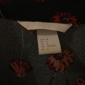 Sort skjorte fra h&m med blomster. Str. 36. Kun brugt 2 gange.