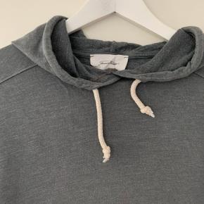 Mørkegrå hoodie med hvide snore fra American Vintage - fed under fx en skindjakke. Lavet af 50% bomuld og 50% viskose. Brugt få gange