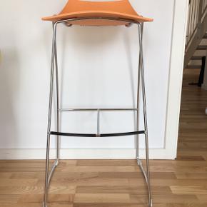 Flot barstol med orange sæde i plastik.