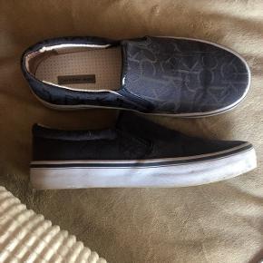 BYD GERNE!  Calvin Klein slip-ons i navy canvas, med ck logoer på. Fremstår som nye, pånær en misfarvning inde i skoen, ved stoffet i hælen.