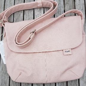 En populær skuldertaske med lang hank, som kan forlænges og bruges på kryds. Det er køn rosa/nude farve og et sødt for. Der er flere lommer, en med lynlås under klappen og 2 indeni tasken i foret. Tasken måler: 35 cm i bredden og 28 cm i højden når tasken er lukket.