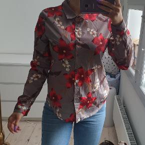 Brun skjorte med røde blomster str small  Den er brugt en gang, fremstår flot og næsten som ny jeg er 171cm høj  Den sælges for 150kr Kan sendes med DAO for 37,50kr