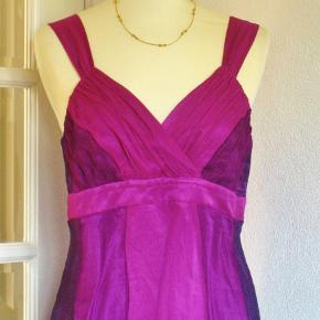 Så lækker designer luxus: SILKE-kjole fra Margit Brandt (mærket i nakken klippet af, da det stak op). Kun brugt en enkelt gang, så den er SOM NY. Yderste lag er 100 % silkechiffon. Inderste lag er lilla polyester.  Brystvidde: 49 cm x 2 (er dog noget flexibel pga V-udskæringen) Vidde under brystet: 46 cm x 2 Hoftevidde: 63 cm x 2 Længde yderste lag: 108 cm. Inderste lag er 5 cm kortere.  Ingen byt, og prisen er fast