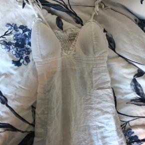 Brugt 1 aften. Købt i Grækenland.  Meget nedringet tætsiddende kjole i str M-L (tror dog den bliver for stram til en L).   Lynlås i siden. Med lommer foran, og stropper som kan bindes og justeres. Skålene foran er forede, så man ikke kan se igennem.   Man får en sindssyg kavalergang i denne kjole!