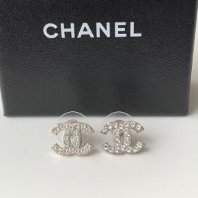 De smukkeste Chanel CC logo ørestikker. Udgået model der ikke fås længere. Original æske medfølger. Købt i Chanel butikken i London. Mål: H 1 cm x B 1,5 cm. Sælges for 3000 kr. Prisen er fast. 🌟Send pb hvis du vil købe🌟  Kun seriøse henvendelser, tak!