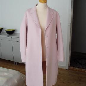 Varetype: Frakke / Ny Farve: Pudderrosa Oprindelig købspris: 999 kr.  Spritny frakke i enkelt design ( Premium Quality),Stadig med mærke. Let uldkvalitet ( 50% uld/ 50% polyester.) Lukkes med 3 store trykknapper Sidelommer og slids bagpå. Uden for.  Længde ca. 105 cm
