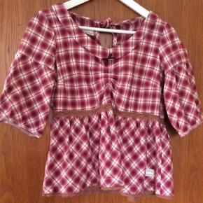 Blusen er str. 1. Stoffet er bomuld, sådan lidt flonelsagtigt. Der er lynlås i siden. Rød og hvid.