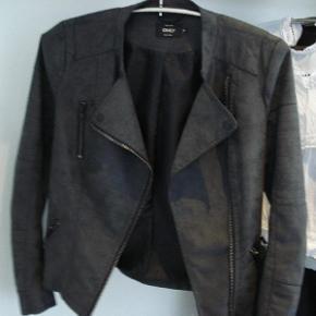 """Koksgrå jakke i imiteret skind (ruskinds look), og i bikerstil. Asymetrisk lynlås hele vejen ned. Lynlås lommer. Lynlås detaljer på brystet. Krave med trykknap detaljer.  """"Only"""", str. 34  Kan maskinvaskes ved 30 °C.  Brugt få gange, og fremstår helt som ny!  skindjakke Farve: Koksgrå"""