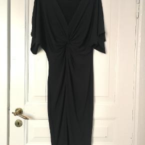 Tætsiddende kjole med slis foran. Går til knæene. Meget behageligt stof der fremhæver ens former. Løse ærmer