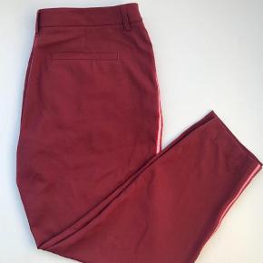 Varetype: Chinos Størrelse: 42/XL Farve: Bordeaux Oprindelig købspris: 1000 kr.  Ubrugte lækre bukser fra Custommade. Str 42 / XL.   Stumpe længde, striper langs siden, metallisk søm, skjult hægte og lynlås. Nypris 1.000,00. Materiale 66% polyester, 30% rayon, 4% elastane.