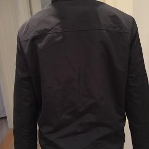 Let vind-agtig jakke, med hætte, som kan rulles sammen. Sporty look med elastik i bunden.