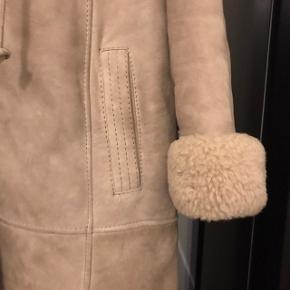 Lang rulamsfrakke i råhvid/natur farve. Har aftagelig hætte med rulam indvendig og opsmøg på ærmerne. Kan passe en str. medium og large.  Fejler intet, men er brugt.