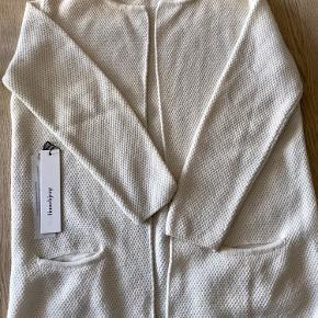 Cremefarvet cardigan, modellen hedder Mary Short Længde ca 78 cm 50% merino uld 50% acryl Bytter desværre ikke