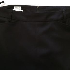 Klassisk sort nederdel. Med små lommer. Lynlås midt bag. Bæltestropper passer til et smalt bælte. Stof som habitjakke.