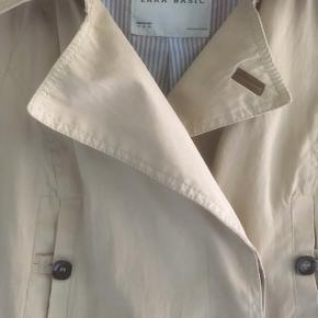 Mærke: Zara Basic Størrelse: M Farve: beige Materiale: 38% Cotton, 54% Polyester og 8 % nylon Frakken: stoffet et blødt med lyseblåt foer. To brystlommen og to sidelommer med lynlås. Lukning af frakken har skjulte knapper. Bælte Stand: Brugt få gange  Sælges kr 125