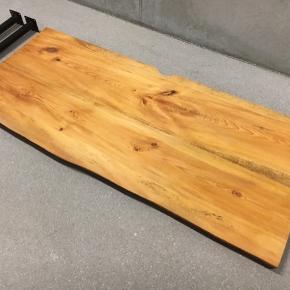 Hjemmelavet skrivebord i fyrretræ. Sammensat af to planker, jævn bagkant med udskæring til ledninger. Rustik forkant. Har fået olie. Bordpladen er ikke helt jævn og hele fladen, da træet har slået sig lidt. Ben og beslag medfølger. Beslag monteres på væggen med skruer.   Bredde 110cm Dybde 47,5 cm Ben længde 70cm