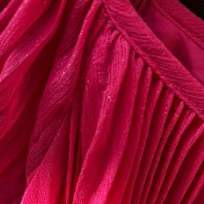 Den yndigste sommerkjole i plisseret stof med blankt for og små søde ærmer, der lige dækker skuldrene.   Farven er pink med små sølvstænk - se foto.   Sender gerne, men du er også velkommen til at hente kontaktfri med mobilepay😊