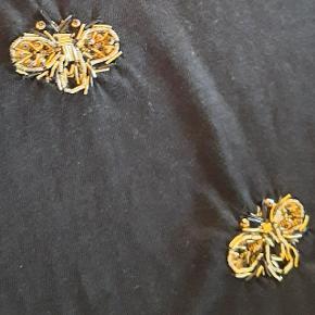 T-shirt fra Mos Mosh str. M 100 % bomuld med gyldne perlebroderier. Længde fra skulder til bund: 64 cm Længde fra halsudskæring til bund: 54 cm Brystmål: 52 cm * 2