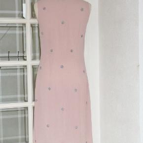 Feminin kjole i to lag og med perlebroderi. Kjolen er skåret under brystet. Materialet er viscose + bomuld. Farve: gl. rosa  Brystvidde: 47 cm x 2 Vidde under brystet: 41 cm x 2 Hoftevidde: 54 cm x 2 Længde:  104 cm (foret er 6 cm kortere)  Bytter ikke med andre ting, og prisen er fast