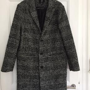Ternet uldfrakke fra H&M. Hul i bunden af den ene lomme i foret indvendig kan nemt sys.