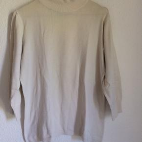 Blød creme-hvid trøje fra Ofelia.  3/4 ærmer. Der står L på mærket, men jeg er selv en XS og kan sagtens passe den (som oversize). Passer derfor XS-L.