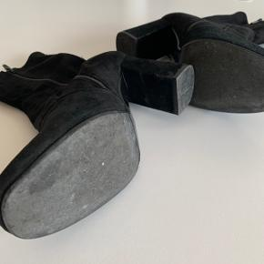 Smukke ruskindsstøvler fra Billi Bi. Skaftet er ikke af ruskind men af et elastisk materiale, som sidder tæt til benet for et slank udseende.  Hælhøjden er ca. 8,5 cm  Brugt få gange og er derfor i god stand. Der er dog kommet et lille hak på indersiden af den ene hæl (se billede 3)