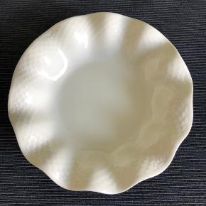 Fin skål i cremefarvet porcelæn fra Bing & Grøndahl nr. 227.  Riflet i kanten indvendig.  Diameter er 18 cm.  Eneste brugstegn er et lille skår på bagsiden, som ikke ses, når skålen står almindeligt fx på et bord