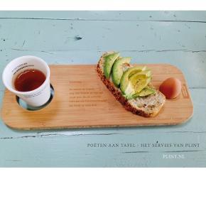 """Morgenmads-planke, PLINT  Denne smukke træ morgenmadsplade er lavet til en dejlig lang poetisk morgenmad fx i sengen - perfekt til søndage og ferier  Med indgraveret digt af den hollandske digter Kreek Daey Ouwens - og med udskæring til kop og æg.  En vidunderlig start på dagen!  Planken er lavet af bambus - god for dig selv (bambus nedbryder bakterier) og god for miljøet (det vokser uden pesticider og kunstgødning).  Mærke: PLINT Træsort: Bambus Størrelse: 40 x 15 x 1,7 cm  Nypris: 23.50 EUR = 175 kr  Ny / aldrig brugt / perfekt stand.  Købt i Amsterdam. Desværre har vi aldrig fået den brugt. og nu skal andre have chancen.  De to første billeder er """"model-fotos""""."""