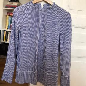 light blue blouse called 'crinckle pop bezina' with white stripes, with a rippled kind of texture. label says 34 but i normally wear a 38 and it's a bit loose on me in a good way