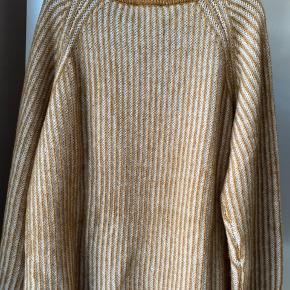 """Lækker strik (""""Cass"""") fra Baum und Pherdgarten.  Strikken har bred halsudskæring og er stribet. Farven hedder Golden Spice melange.  Mål: Bryst : 60cm, længde: 64 cm,  ærme (fra halsudskæring): 65 cm.  Den er lavet i 55% uld, 18% bomuld og 27% genanvendt polyester.  Aldrig brugt. Sælger kun og bytter ikke."""