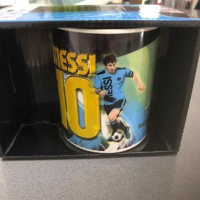 Messi  fan krus, i original indpakning ( æske), med motiver på begge sider. Aldrig brugt. Fra ikke ryger hjem.