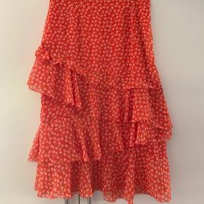 Sælger denne super smukke nederdel fra H&M. Den er i en orange farve med rødlige farver. Derfor kan det godt ligne at den er rød på billederne.  Den har fire lag af flæser både foran og bagpå. Den har et underskørt, så den er derfor ikke gennemsigtig🧡 I Venstre side har den en skjult lynlås.   Den måler 2 x 39 cm i taljen, men den har som sagt en lynlås i siden, så den er til at komme i🤠 Den har en længde på 71 cm   Nederdelen er kun prøvet på og aldrig brugt. Fremstår derfor helt ny🌸
