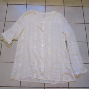 Flot hvid skjorte fra Soyaconcept, med hvide broderier, små perlemorsknapper og opsmøg til ærmer. Vist med en sort top under (medfølger ikke), for at vise kontrasten med en farvet top. Brugt og vasket 1 gang, den øverste knap mangler, der medfølger en ny på vaskemærket, men tror egentligt ikke man knapper den øverste.