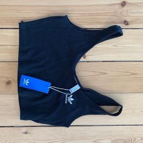 Kort Adidas top i sort. Mavebæusw. Str. Small. Aldrig brugt og med mærke. Køber betaler for forsendelse :)