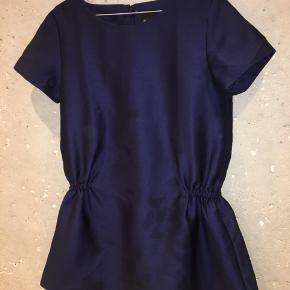 """Smukkeste fuldforede mørkeblå kjole fra Six Ames i str. 38/M. Materialet er en afstivet kvalitetssatin der minder om glat thaisilke. Holder en ren form og lige silhuet på nær hvor skørtet er placeret  (på hoften). Skørtet er plisseret bagpå også og kun """"åbent"""" foran. Smuk farve.   Brugt 1-2 gange og er uden brugstegn.   Mængderabat gives naturligvis 😄✨"""