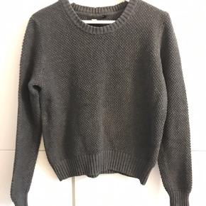 En kort fin sweater i mørkegrå. Fejler intet.