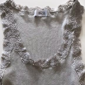 Helt ny Snob silketop med blondekant og i sølvglimmer. 70% silke, 30% bomuld, lidt længere end Rosemunde top.  Sender pp