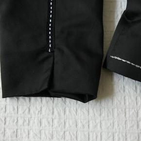 Sort satin jakke med hvide stikninger og slids forneden på ærmerne.  Satin jakke Farve: sort