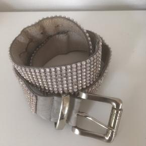 Bælte fra Croute De Cuir, Made in France. 85 cm lang.  Læder på bagsiden og sølv perler på forsiden Flot bælte.  Stand: er slidt på bagsiden ved tre af hullerne, men det ses ikke på forsiden  Sælges 50 kr