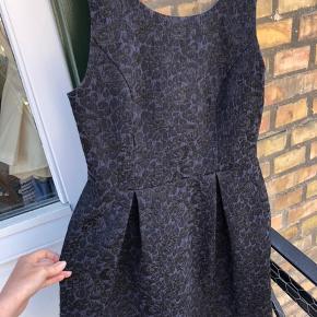 Kjolen har en meget mørkeblå bund med sorte blomster på og glimmer. Meget pæn med åben ryg😍
