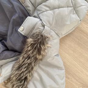 Skøn halvlang dueblå vinterjakke med to lynlåslommer foran.  Jakken lukkes med kraftig lynlås med vindfang over, der lukkes med trykknapper. Jakken har også vindfang ved håndleddene, og den har aftagelig hætte med fake pels, pelsen kan også tages af hvis man ønsker det. Materialet er vandafvisende.