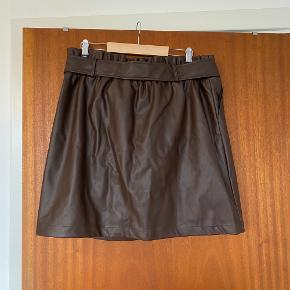 Sælger denne fine imiteret lædernederdel i brun. Den har et bindebånd i livet og lukket med en skjult lynlås foran. Er brugt én gang  Kan sendes eller afhentes på Frederiksberg  #30dayssellout