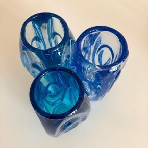 Smukke blå farver. Unikke ovale retro vaser i glas i 3 forskellige nuancer. Smukke til dine blomster eller som et fint indslag i vindues karmen. Højden måler 15cm og bredden og dybden 7cm.  De er ret tunge og vejer hver 640gram. Pr.stk.