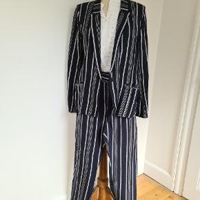 Loose snit cool jakkesæt i mørkeblå med hvide striber. Jakken er 38 og bukserne 40 men jakken er løs snit og sættet er bedst til str 40. Næsten butiksny. Sælges da den er for stor til mig nu, da jeg er størrelse 34. Blusen tilhører ikke med.