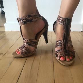 Sælger disse lækre stiletter / sandaler, der er brugt en håndfuld gange. Se billeder for standen.   Mærket er Koala Bay.   Hælhøjde 10 cm. Lukkes med lynlås op midt på foden.   Størrelsessvarende. 25 cm i indvendig længde.   Køber betaler evt porto. Jeg sender med Dao.