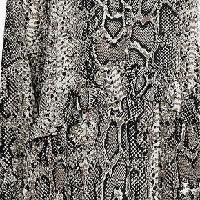 Tunika i grå slangeskindsmønster fra Vero Moda, løst snit med flæsekant i taljen og betrukne knapper foroven. Lange ærmer med elastik og flæsekant. Fremstillet i tynd, vævet kvalitet. Længde ca. 81 cm.  ALDRIG BRUGT.
